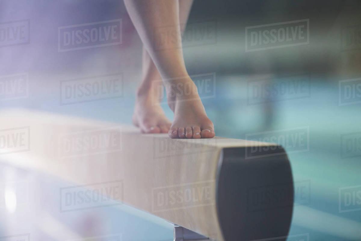 bare feet of female gymnast performing on balance beam - stock photo