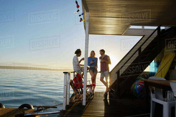 Young adult friends hanging out on summer houseboat on ocean Royalty-free stock photo