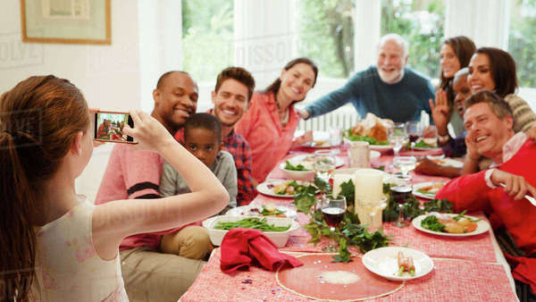 Girl with camera phone photographing multi-ethnic family at Christmas dinner table Royalty-free stock photo