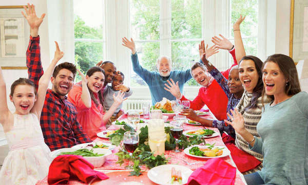 Portrait enthusiastic multi-ethnic multi-generation family waving at Christmas dinner table Royalty-free stock photo