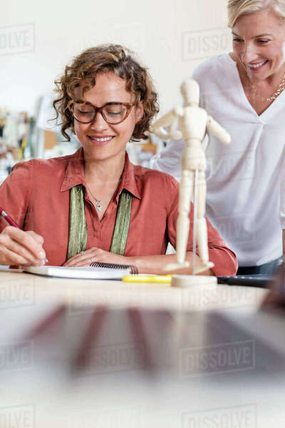 Female design professionals with artist's figure sketching in office Royalty-free stock photo