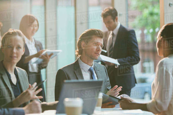 Serious businessman talking to businesswoman in conference room meeting Royalty-free stock photo