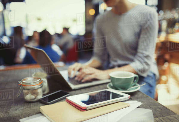 Creative businesswoman working at laptop behind digital tablet in cafe Royalty-free stock photo
