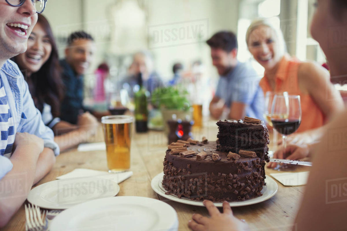 Woman Serving Chocolate Birthday Cake To Friends At Restaurant Table