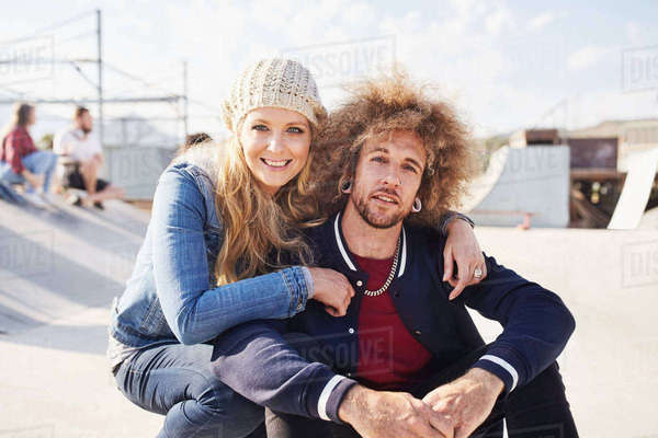 Portrait smiling couple at sunny skate park Royalty-free stock photo