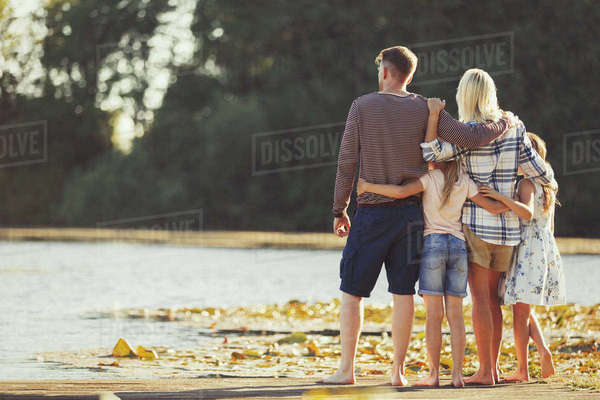 Family hugging at sunny lakeside Royalty-free stock photo