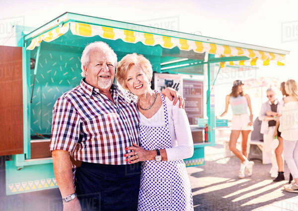 Portrait smiling senior business owners outside sunny food cart Royalty-free stock photo