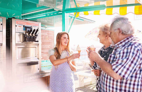 Smiling young woman serving ice cream to senior couple outside food cart Royalty-free stock photo