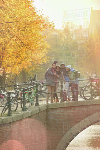 Friends taking selfie with selfie stick on autumn bridge over canal in Amsterdam Royalty-free stock photo