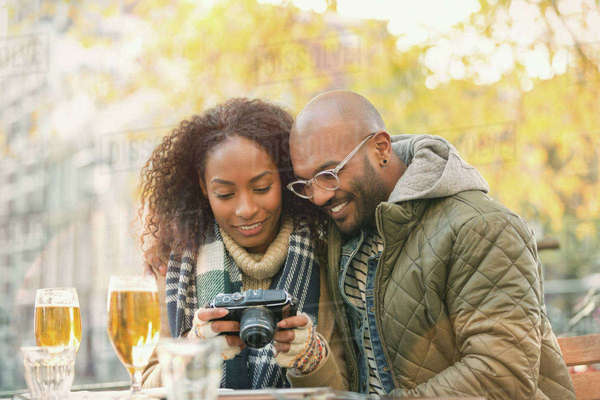 Young couple viewing digital camera and drinking beer at autumn sidewalk cafe Royalty-free stock photo