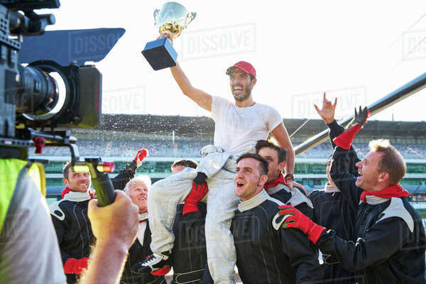 Racing team celebrating victory carrying race car driver with trophy on shoulders Royalty-free stock photo