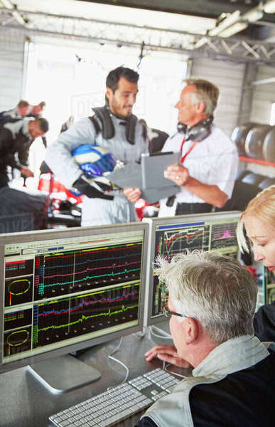Formula one team reviewing diagnostics in repair garage Royalty-free stock photo