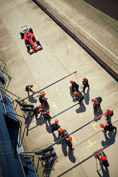 Pit crew ready for nearing formula one race car in pit lane Royalty-free stock photo