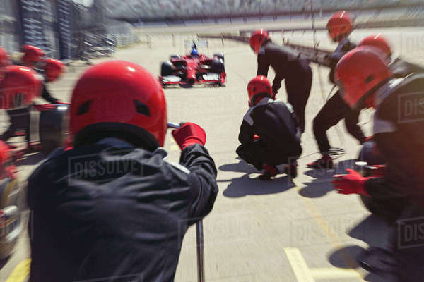 Pit crew ready for nearing formula one race car driver in pit lane Royalty-free stock photo
