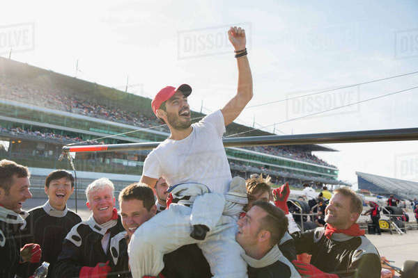 Formula one racing team carrying cheering driver on shoulders, celebrating victory on sports track Royalty-free stock photo
