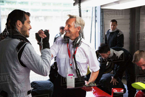 Manager and formula one driver celebrating, handshaking in repair garage Royalty-free stock photo