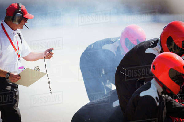 Manager with stopwatch timing formula one pit crew practice session Royalty-free stock photo