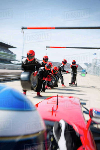 Pit crew with tires ready for nearing formula one race car in pit lane Royalty-free stock photo