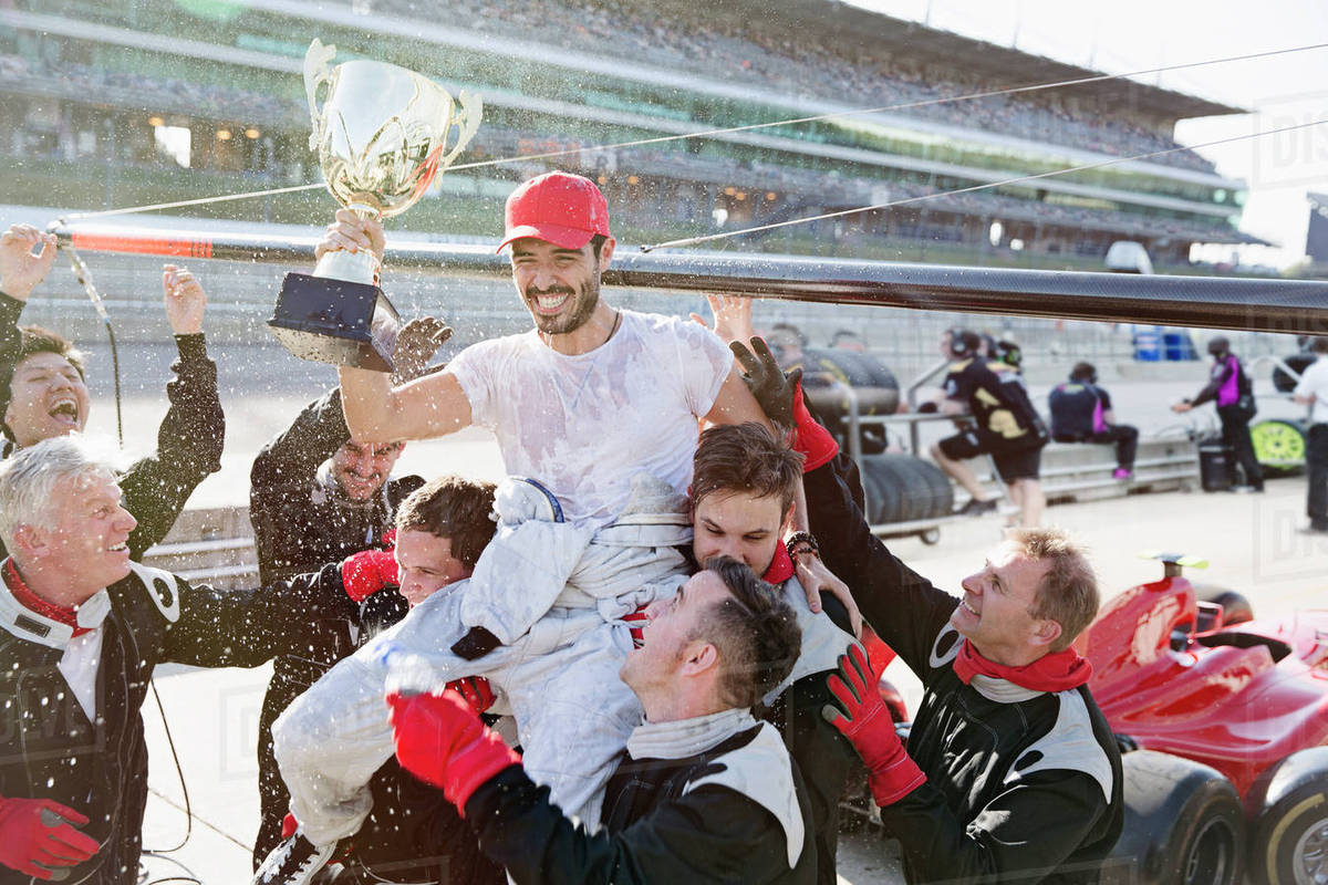 Formula one racing team carrying driver with trophy on shoulders, celebrating victory on sports track Royalty-free stock photo