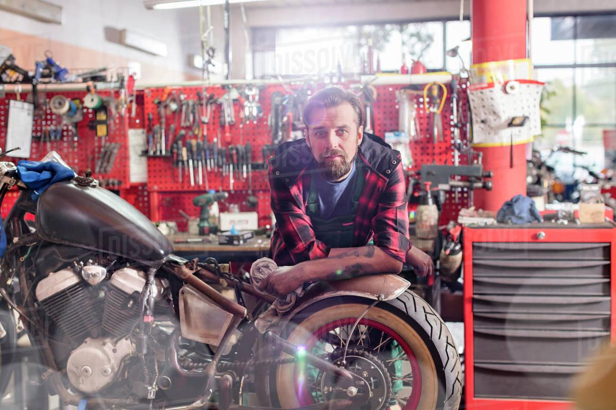 portrait serious confident motorcycle mechanic in workshop