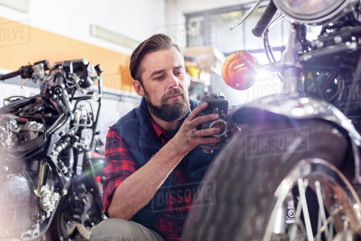 motorcycle mechanic doing diagnostic test on motorcycle in workshop