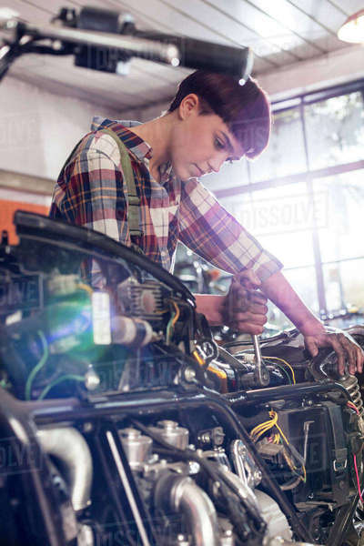 Female motorcycle mechanic repairing motorcycle in workshop Royalty-free stock photo