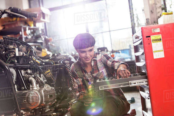 Female motorcycle mechanic retrieving tools in toolbox in workshop Royalty-free stock photo