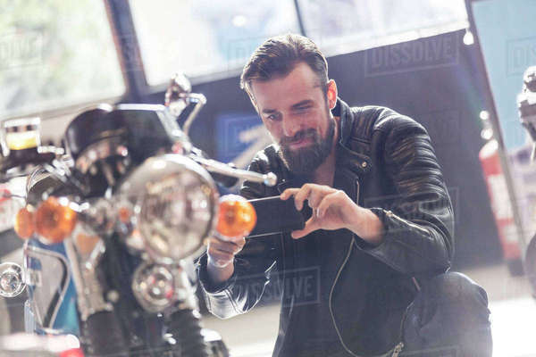 Man with camera phone photographing motorcycle in shop Royalty-free stock photo