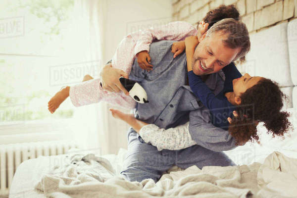 Multi-ethnic daughters playing and tackling father on bed Royalty-free stock photo