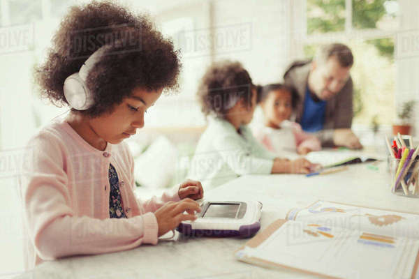 Girl with headphones using digital tablet doing homework at table Royalty-free stock photo