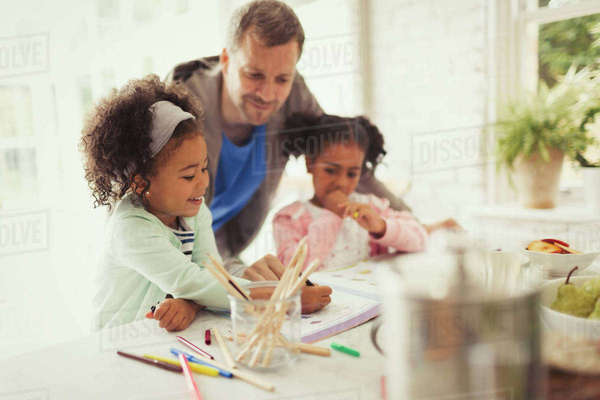 Multi-ethnic father and daughters coloring Royalty-free stock photo