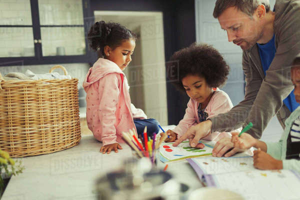 Multi-ethnic father and daughters coloring and using activity books in kitchen Royalty-free stock photo