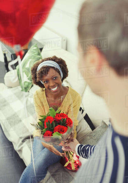 Husband giving Valentine's Day rose bouquet and balloon to wife Royalty-free stock photo