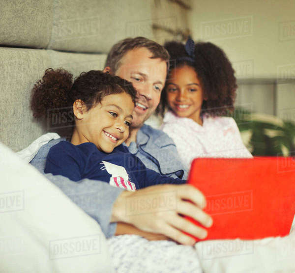 Multi-ethnic father and daughters using digital tablet on bed Royalty-free stock photo