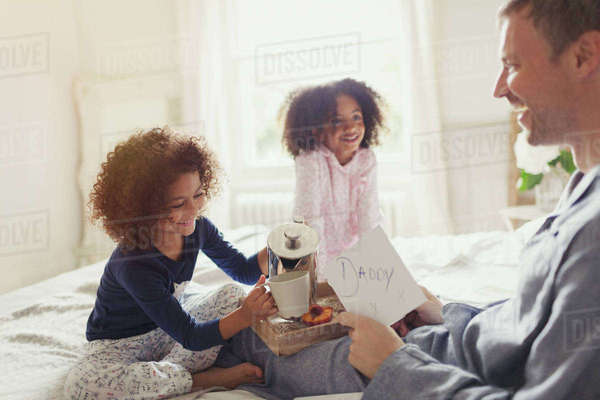 Daughters serving coffee and card to father in bed on Father's Day Royalty-free stock photo