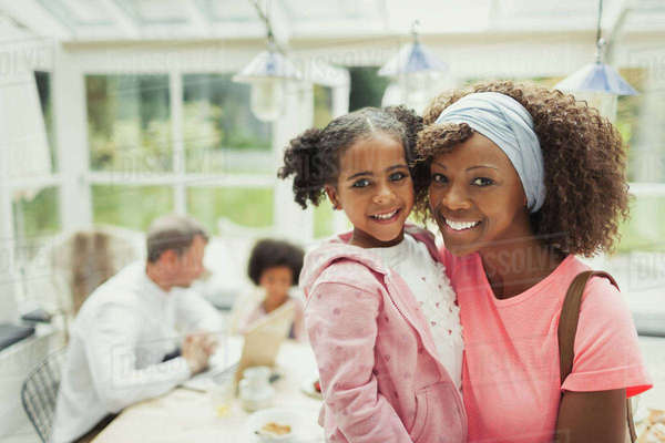 Portrait smiling mother and daughter hugging in kitchen Royalty-free stock photo