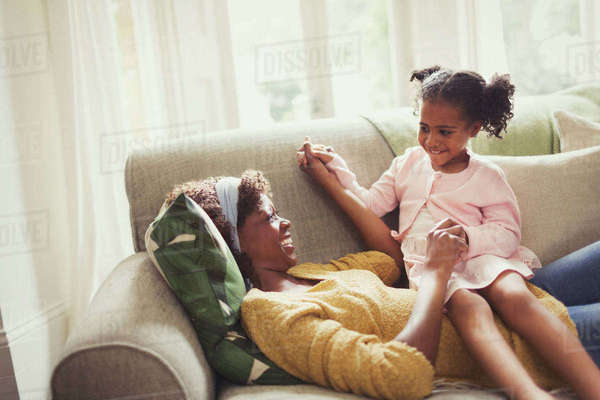 Playful mother and daughter holding hands on sofa Royalty-free stock photo