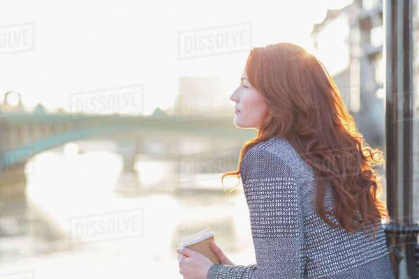Serene businesswoman with red hair drinking coffee at urban waterfront Royalty-free stock photo