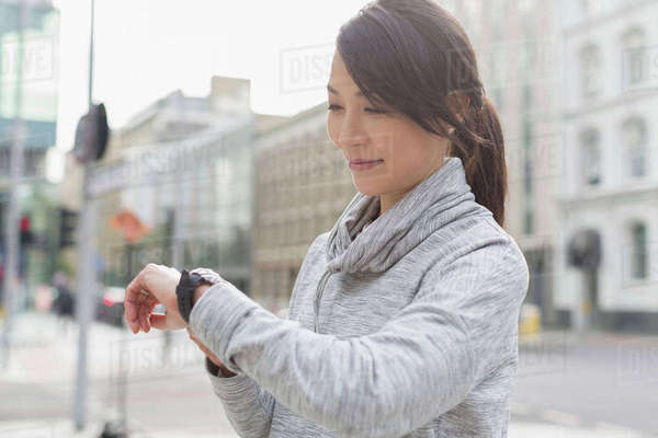 Smiling female runner checking wristwatch on urban sidewalk Royalty-free stock photo