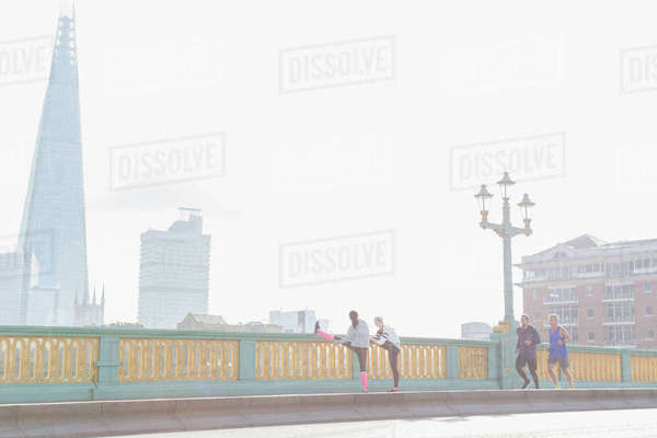 Runners running and stretching on sunny, foggy urban bridge, London, UK Royalty-free stock photo
