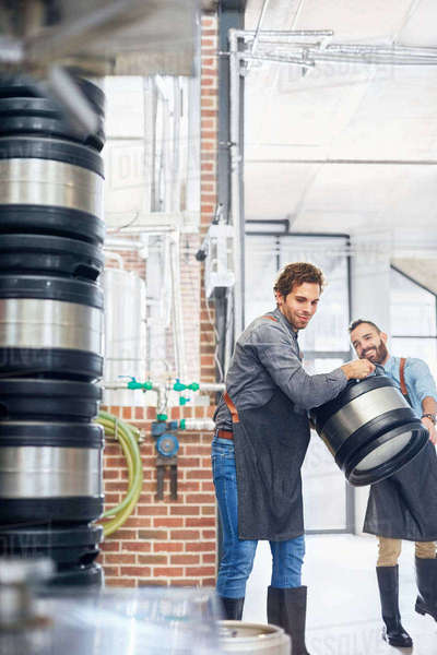 Male brewers carrying kegs in brewery Royalty-free stock photo