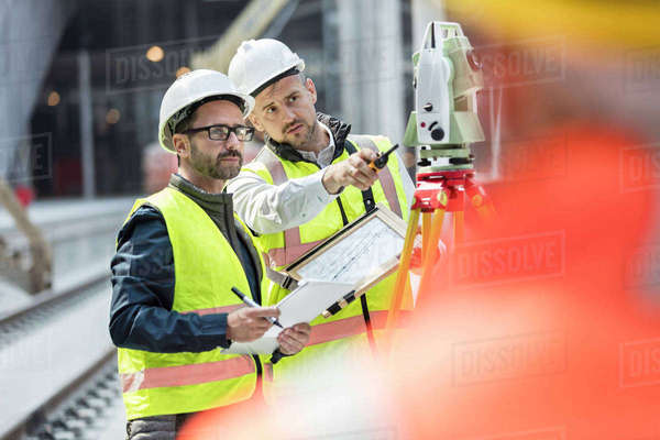 Male engineers using theodolite at construction site Royalty-free stock photo