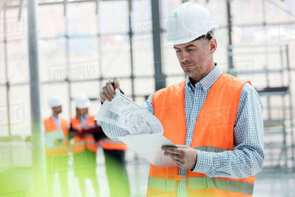Male engineer reviewing blueprints on clipboard at construction site Royalty-free stock photo