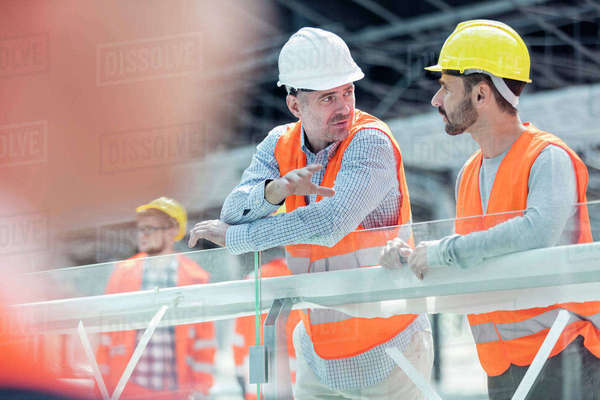 Male foreman and construction worker talking at construction site Royalty-free stock photo