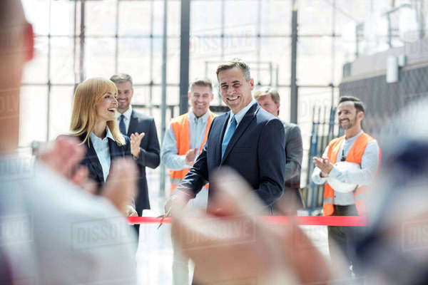 Smiling businessman and businesswoman cutting ribbon at new construction site ceremony Royalty-free stock photo