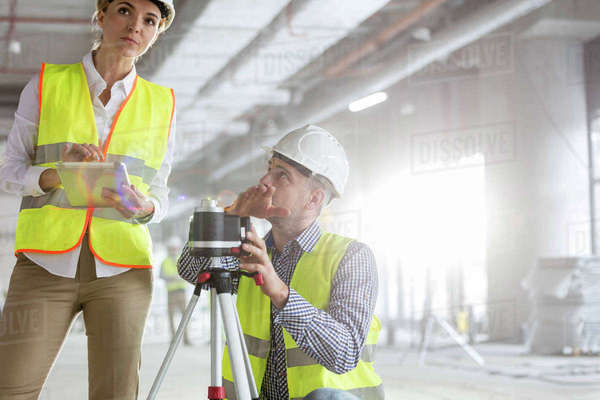 Engineers with digital tablet and theodolite surveying construction site Royalty-free stock photo