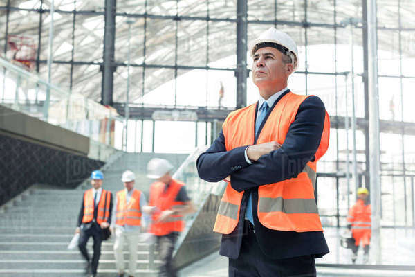 Serious businessman wearing hard-hat at construction site Royalty-free stock photo