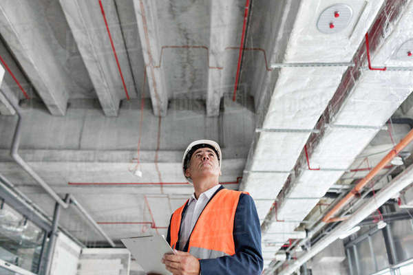 Foreman with clipboard looking up at construction site Royalty-free stock photo