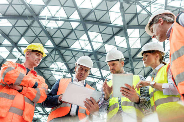 Foreman and construction workers using digital tablets in meeting at construction site Royalty-free stock photo