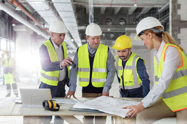 Engineers reviewing blueprints at construction site Royalty-free stock photo
